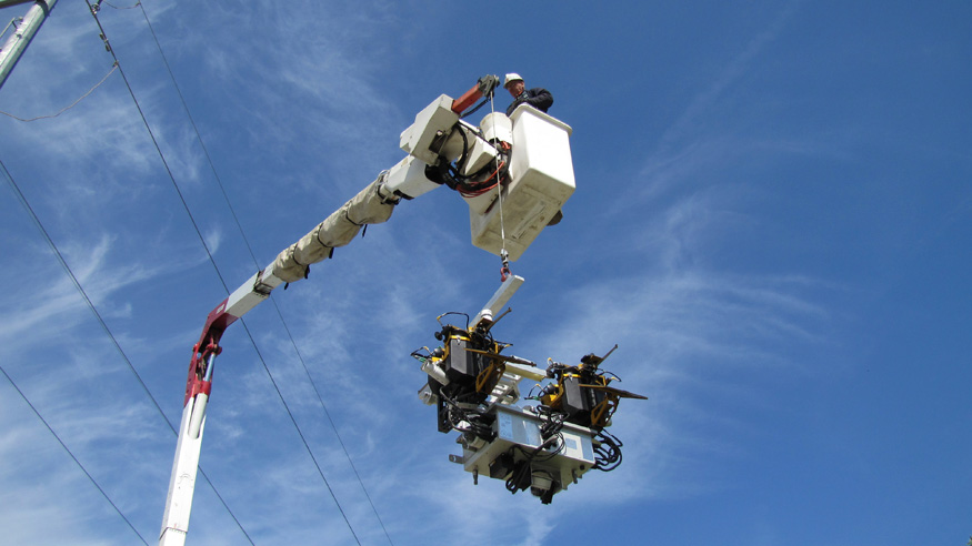 A technician uses a bucket truck as he prepares to attach Ti to a transmission line. The robot's diagnostic equipment includes  high-definition cameras, LIDAR sensors, electromagnetic interference detectors along with data processing, global positioning, and communications systems.